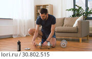 Купить «man assembling dumbbells at home», видеоролик № 30802515, снято 15 мая 2019 г. (c) Syda Productions / Фотобанк Лори