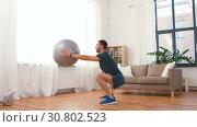 Купить «man exercising and doing squats with ball at home», видеоролик № 30802523, снято 15 мая 2019 г. (c) Syda Productions / Фотобанк Лори