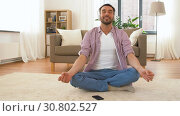 Купить «man in headphones meditating in lotus pose at home», видеоролик № 30802527, снято 15 мая 2019 г. (c) Syda Productions / Фотобанк Лори