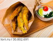 Купить «Fried in batter anchovies with creamy cheese sauce and greens», фото № 30802691, снято 23 августа 2018 г. (c) Яков Филимонов / Фотобанк Лори