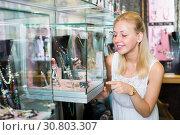 Купить «Female choosing bijouterie in glass showcase in boutique», фото № 30803307, снято 10 декабря 2019 г. (c) Яков Филимонов / Фотобанк Лори