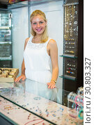 Купить «Woman seller standing next to glass showcase», фото № 30803327, снято 22 октября 2019 г. (c) Яков Филимонов / Фотобанк Лори