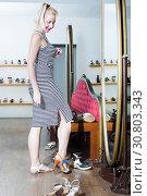 Купить «Young woman customer selecting on pair of variety sandals», фото № 30803343, снято 21 мая 2019 г. (c) Яков Филимонов / Фотобанк Лори