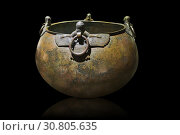 Phrygian bronze couldron with decorated winged figure handles. From Gordion. Phrygian Collection, 8th century BC - Museum of Anatolian Civilisations Ankara. Turkey. Against a black background. (2012 год). Редакционное фото, фотограф Funkystock / age Fotostock / Фотобанк Лори