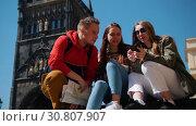Купить «Young friends travelers sitting on a background of Bridge Tower of Charles Bridge and searching for a way to go in their phone navigator and on the map», видеоролик № 30807907, снято 16 сентября 2019 г. (c) Константин Шишкин / Фотобанк Лори