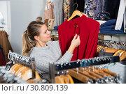 Купить «Girl holding red blouse on hanger», фото № 30809139, снято 6 декабря 2018 г. (c) Яков Филимонов / Фотобанк Лори