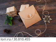 mockup Christmas kraft gift boxes with xmas wooden toys on wooden background. Top view for greeting card with place for text. Стоковое фото, фотограф Happy Letters / Фотобанк Лори