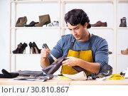 Купить «Young man repairing shoes in workshop», фото № 30810867, снято 22 октября 2018 г. (c) Elnur / Фотобанк Лори