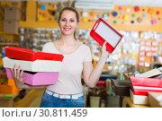 Купить «Woman is demonstrarting red and white boxes for trifle», фото № 30811459, снято 19 апреля 2017 г. (c) Яков Филимонов / Фотобанк Лори