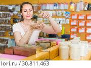 Купить «Smiling woman is choosing small boxes for gifts», фото № 30811463, снято 19 апреля 2017 г. (c) Яков Филимонов / Фотобанк Лори