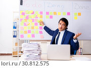 Купить «Young handsome employee in front of whiteboard with to-do list», фото № 30812575, снято 16 октября 2018 г. (c) Elnur / Фотобанк Лори