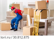 Купить «Young male contractor with boxes working indoors», фото № 30812875, снято 1 февраля 2019 г. (c) Elnur / Фотобанк Лори