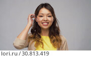 Купить «portrait of smiling asian woman touching her hair», видеоролик № 30813419, снято 17 мая 2019 г. (c) Syda Productions / Фотобанк Лори