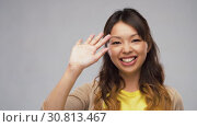 Купить «smiling asian woman waving hand», видеоролик № 30813467, снято 17 мая 2019 г. (c) Syda Productions / Фотобанк Лори