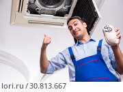 Young repairman repairing ceiling air conditioning unit. Стоковое фото, фотограф Elnur / Фотобанк Лори