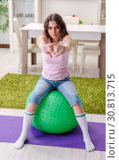 Купить «Young beautiful woman doing exercises at home», фото № 30813715, снято 14 декабря 2018 г. (c) Elnur / Фотобанк Лори