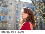 Купить «Young brunette woman with sensual lips in red shirt enjoying spring breeze outdoors while the sun is shining», фото № 30813791, снято 30 марта 2019 г. (c) Ольга Балынская / Фотобанк Лори