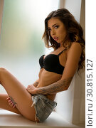Купить «Slim tattooed girl sitting on the window shot», фото № 30815127, снято 6 августа 2017 г. (c) Гурьянов Андрей / Фотобанк Лори