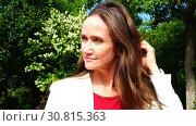 Купить «A girl in a white jacket takes off sunglasses in the open air», видеоролик № 30815363, снято 4 ноября 2017 г. (c) Aleksandr Sulimov / Фотобанк Лори