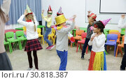 Купить «Happy kids and female teacher in funny hats and festive accessories dancing together in schoolroom», видеоролик № 30818387, снято 30 января 2019 г. (c) Яков Филимонов / Фотобанк Лори