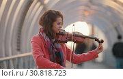 Купить «Smiling young woman playing violin on the overhead passage. Tuning the violin», видеоролик № 30818723, снято 3 апреля 2020 г. (c) Константин Шишкин / Фотобанк Лори