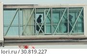 Купить «Silhouettes of people going aboard through the glass passage to the airplane», видеоролик № 30819227, снято 3 апреля 2020 г. (c) Константин Шишкин / Фотобанк Лори