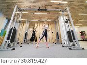 Купить «Athlete woman is working on the simulator with a partner in gym», фото № 30819427, снято 6 марта 2019 г. (c) Константин Шишкин / Фотобанк Лори