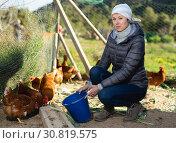 Купить «Young woman farmer caring for poultry», фото № 30819575, снято 18 марта 2019 г. (c) Яков Филимонов / Фотобанк Лори