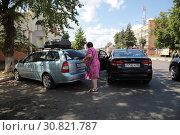 Звенигород, женщина закрывает багажник автомобиля на улице Московская (2019 год). Редакционное фото, фотограф Дмитрий Неумоин / Фотобанк Лори