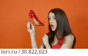 Купить «A beautiful young brown-haired girl examines a pair of red shoes. Emotions. Art portrait in a studio on an orange background», видеоролик № 30822023, снято 8 апреля 2019 г. (c) Ольга Балынская / Фотобанк Лори