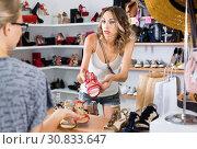 Купить «Female unpleasantly surprised by price for shoes in store.», фото № 30833647, снято 17 августа 2017 г. (c) Яков Филимонов / Фотобанк Лори