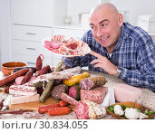 Купить «man posing with a plate of cold cuts», фото № 30834055, снято 17 ноября 2016 г. (c) Татьяна Яцевич / Фотобанк Лори