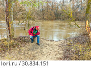A tourist sits thinking on the bank of the river during the spring flood. Стоковое фото, фотограф Акиньшин Владимир / Фотобанк Лори