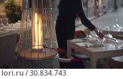 Купить «pyramid-shaped outdoor gas heaters in a cafe. The waiter lights candles», видеоролик № 30834743, снято 10 мая 2019 г. (c) Ирина Мойсеева / Фотобанк Лори