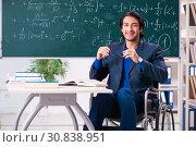 Купить «Young handsome man in wheelchair in front of chalkboard», фото № 30838951, снято 23 ноября 2018 г. (c) Elnur / Фотобанк Лори