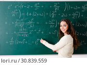 Купить «Young female math teacher in front of chalkboard», фото № 30839559, снято 2 ноября 2018 г. (c) Elnur / Фотобанк Лори
