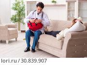Купить «Young handsome doctor visiting female patient at home», фото № 30839907, снято 3 декабря 2018 г. (c) Elnur / Фотобанк Лори