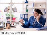 Купить «Young handsome employee in the office», фото № 30840163, снято 1 марта 2019 г. (c) Elnur / Фотобанк Лори