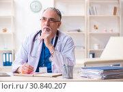 Купить «Old male doctor working in the clinic», фото № 30840207, снято 15 марта 2019 г. (c) Elnur / Фотобанк Лори