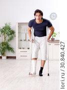 Купить «Leg injured young man suffering at home», фото № 30840427, снято 15 января 2019 г. (c) Elnur / Фотобанк Лори
