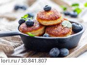 Купить «Cheese pancakes and blueberries in cast iron pan», фото № 30841807, снято 20 февраля 2018 г. (c) Марина Сапрунова / Фотобанк Лори