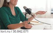 Купить «woman with microphone recording podcast at studio», видеоролик № 30842071, снято 20 мая 2019 г. (c) Syda Productions / Фотобанк Лори