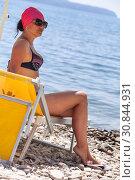 Купить «Загорелая взрослая женщин сидит на желтом лежаке, солнцезащитные очки на глазах, пляж», фото № 30844931, снято 23 июля 2018 г. (c) Кекяляйнен Андрей / Фотобанк Лори