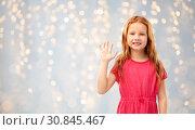 Купить «smiling red haired girl waving hand over lights», фото № 30845467, снято 9 марта 2019 г. (c) Syda Productions / Фотобанк Лори