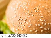 Купить «close up of hamburger bun crust with sesame seeds», фото № 30845483, снято 21 мая 2015 г. (c) Syda Productions / Фотобанк Лори