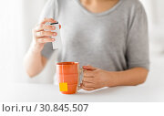 close up of woman adding sweetener to cup of tea. Стоковое фото, фотограф Syda Productions / Фотобанк Лори