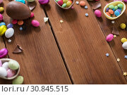 Купить «chocolate eggs and candy drops on wooden table», фото № 30845515, снято 22 марта 2018 г. (c) Syda Productions / Фотобанк Лори