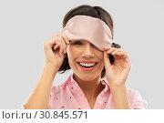 Купить «happy young woman peeking from under sleeping mask», фото № 30845571, снято 6 марта 2019 г. (c) Syda Productions / Фотобанк Лори