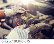 Купить «auto mechanic man with multimeter testing battery», фото № 30845675, снято 1 июля 2016 г. (c) Syda Productions / Фотобанк Лори