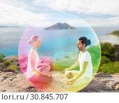 Купить «couple doing yoga in lotus pose with rainbow aura», фото № 30845707, снято 6 августа 2014 г. (c) Syda Productions / Фотобанк Лори